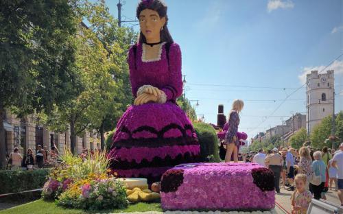 Szinyei Merse Pál Lila ruhás nőfigurája a Fórum virágkocsiján